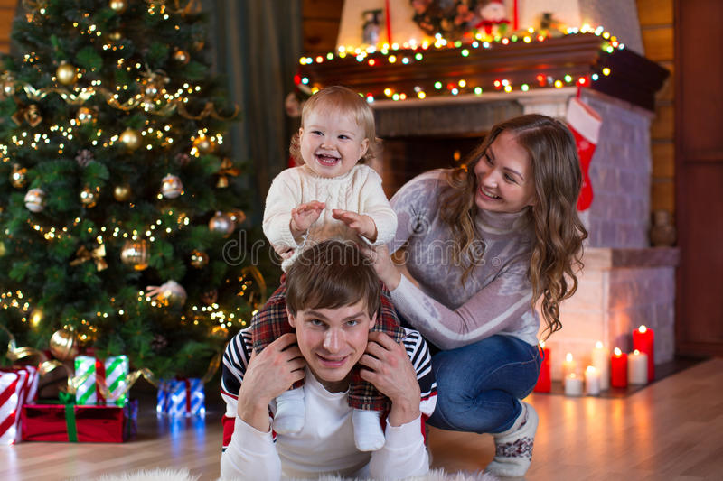 Christmas, x-mas, family, people, happiness concept - happy parents playing with pretty baby. Boy stock photo