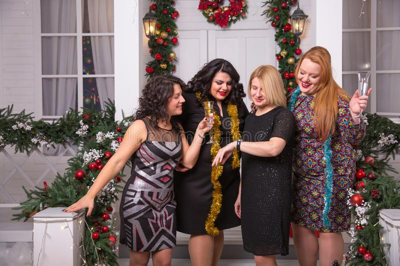 Christmas, x-mas, New Year, winter, happiness concept - four smiling women look at the clock or watch. Christmas, x-mas, New Year, winter, happiness concept stock photography
