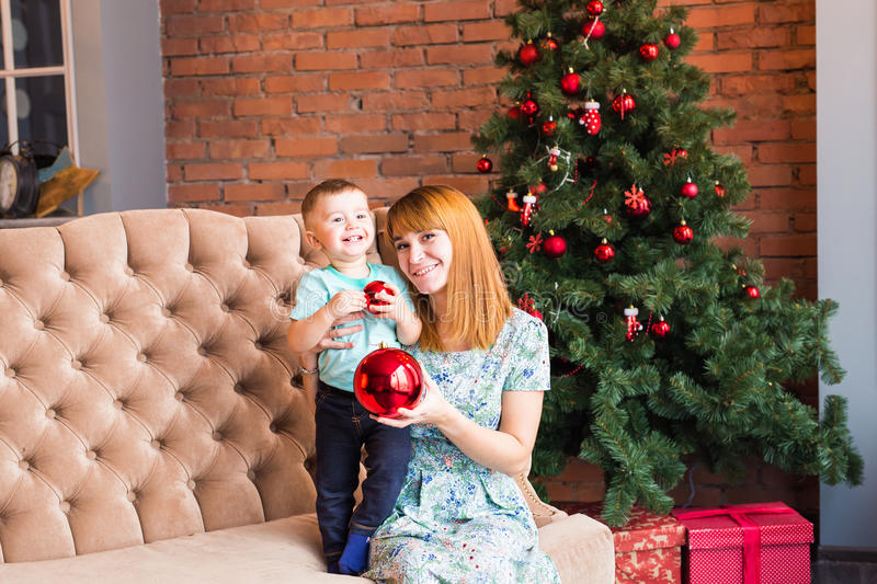 Christmas, x-mas, winter, family, people, happiness concept - happy mother with adorable baby boy. Christmas, x-mas, winter, family, people, happiness concept royalty free stock photography