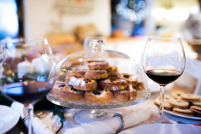 Christmas meal on a table. Pastry and red wine. Christmas meal laid on a table in decorated dining room. Jelly cookies, pastry on cake tray and glass of red royalty free stock image