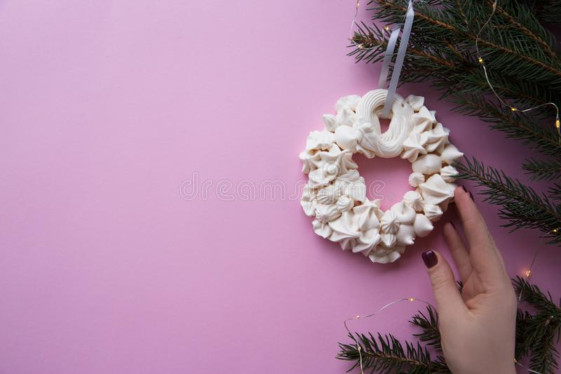 Christmas meringue wreath with hand on the fir branch on the pink color background. Flat lay royalty free stock photo