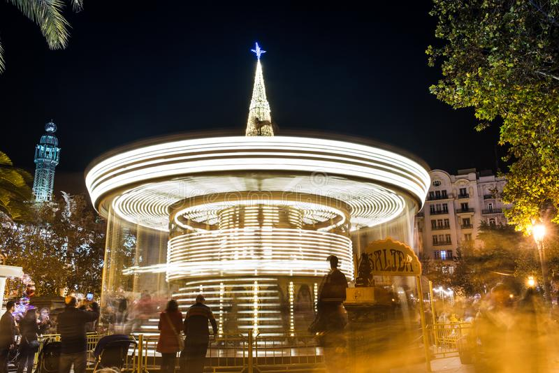 Christmas merry-go-round in the square. Christmas carousel with lights in motion at central square of Valencia, Spain royalty free stock image