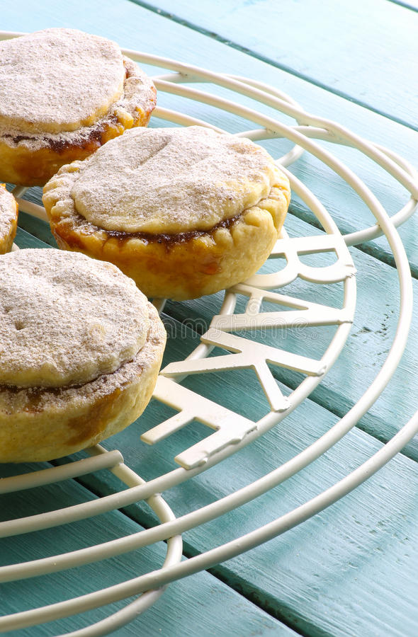 Christmas Mince Pies on Cooling Rack Turquoise Background royalty free stock image