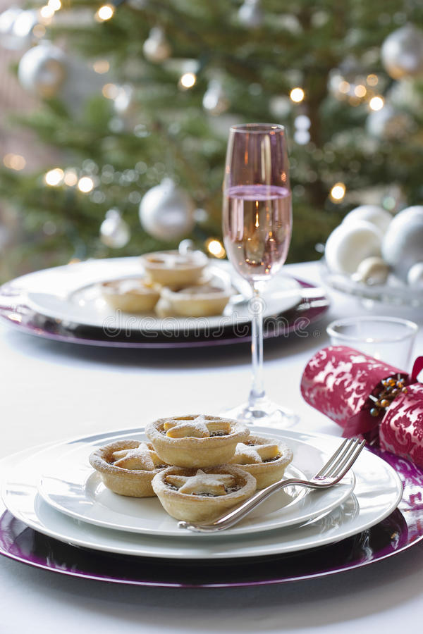 Christmas Mince Pies. Cracker and champagne flute on dining table royalty free stock photos