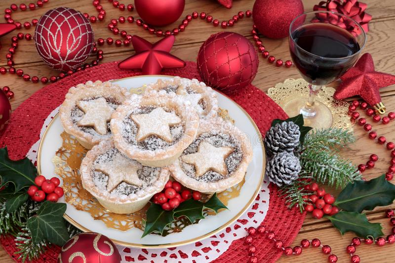 Christmas Mince Pies and Wine. Christmas mince pies with red wine red bauble decorations, holly, ivy, pine cones and fir on oak wood background stock image