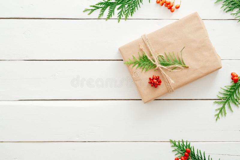 Christmas minimal composition. Xmas present wrapped kraft paper and fir tree branches on wooden white background. New year, stock image