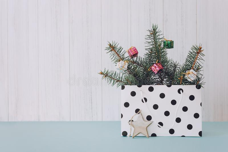 Christmas minimal flat lay composition with fir branches, shiny christmas balls, wooden star  in polka dot gift bag on pastel royalty free stock image