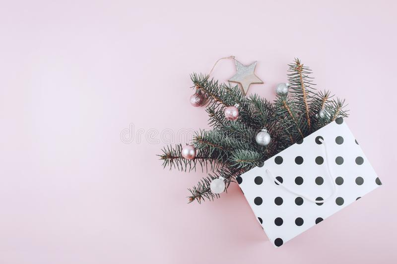Christmas minimal flat lay composition with fir branches, shiny christmas balls, wooden star  in polka dot gift bag on pastel stock images