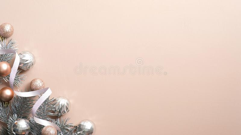 Christmas minimal flat lay composition. Xmas frame of silver and bronze balls, pine tree branches, ribbon on copper background. Top view, copy space. Winter stock photo