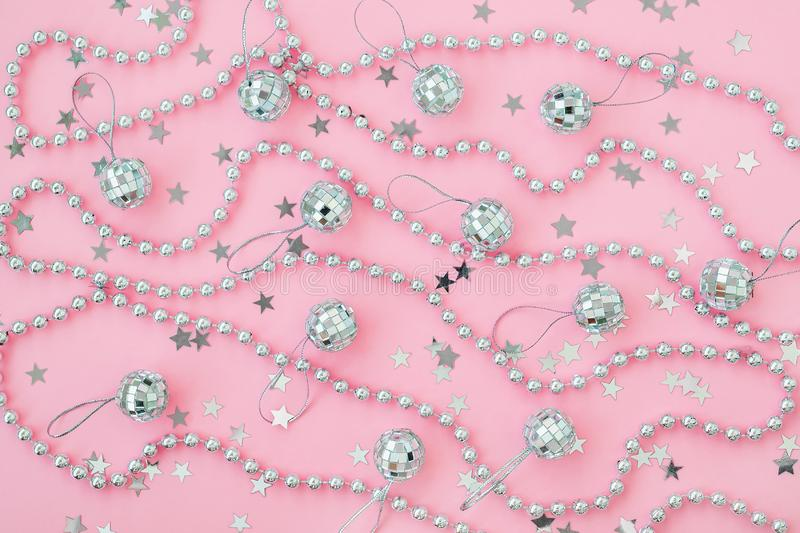 Christmas mirror balls and bead garland on a pastel pink background with silver stars. Festive flat lay for Christmas and New Year royalty free stock image