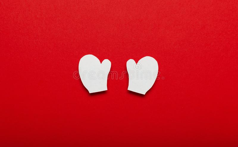 Christmas mittens made of paper on red background. Merry Christmas advertising for covers, invitations, posters, banners, flyers,. Placards stock photo