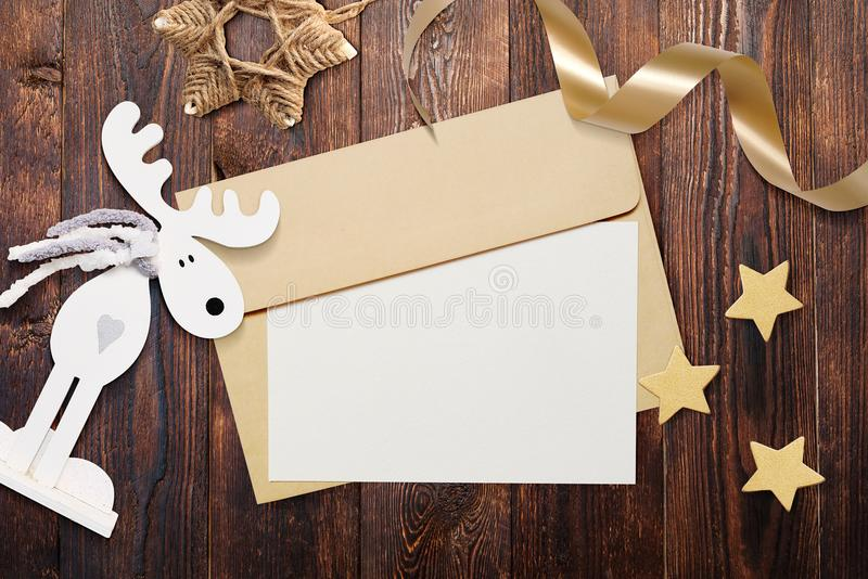 Christmas mockup envelope with blank paper on brown wooden background. Letter to Santa Claus. Christmas winter setting - stock photos
