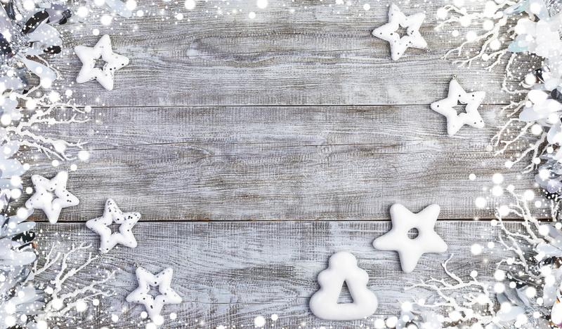 Christmas mockup. Frame of white Christmas stars, gingerbreads, twigs, tinsel and snow on white wooden background. Christmas festive mockup in white. Xmas royalty free stock photos