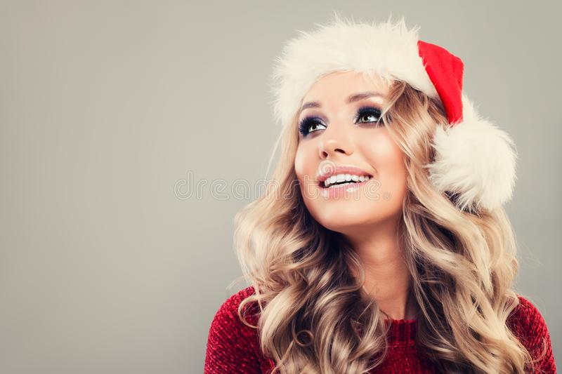 Christmas Model Woman Looking Up. Cute Girl wearing Santa Hat on Background with Copy space stock image
