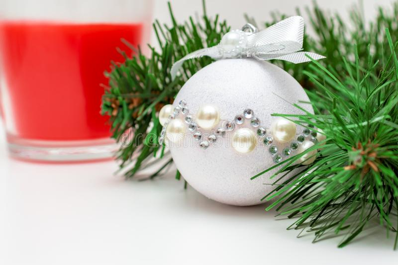 Christmas mood - a branch of fir pine tree, shiny decorative christmas ball and a red candle on white background with copy space royalty free stock photography