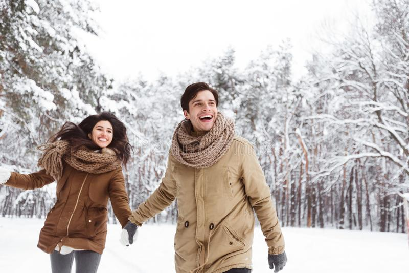 Cheerful Couple Walking Through Winter Forest Holding Hands stock images