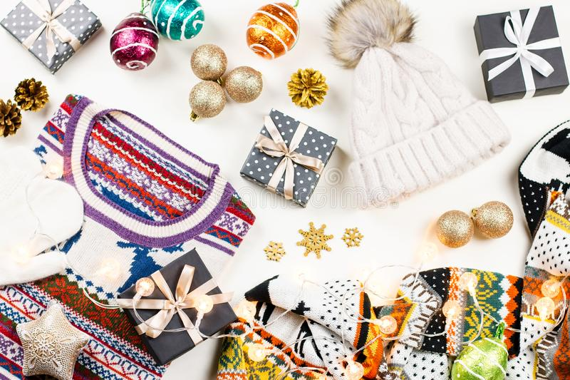 Christmas mood composition with Christmas sweater, hat, presents and lights. Winter concept flat lay, top view royalty free stock photos