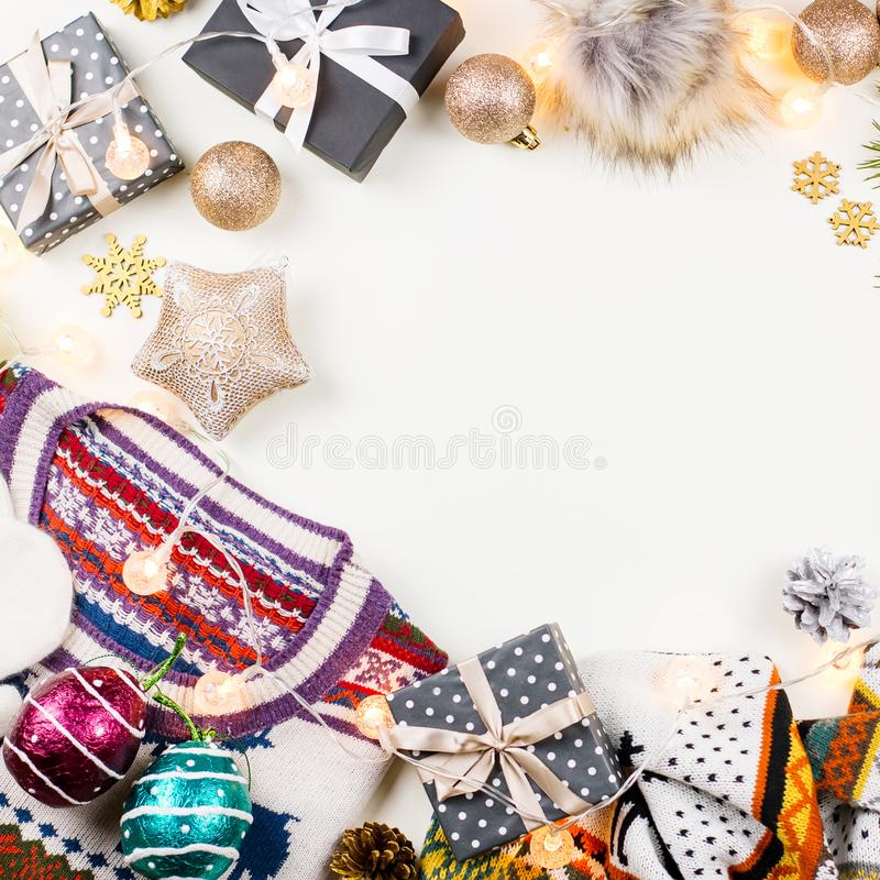 Christmas mood composition with Christmas sweater, hat, presents and lights. Winter concept flat lay, top view royalty free stock photography