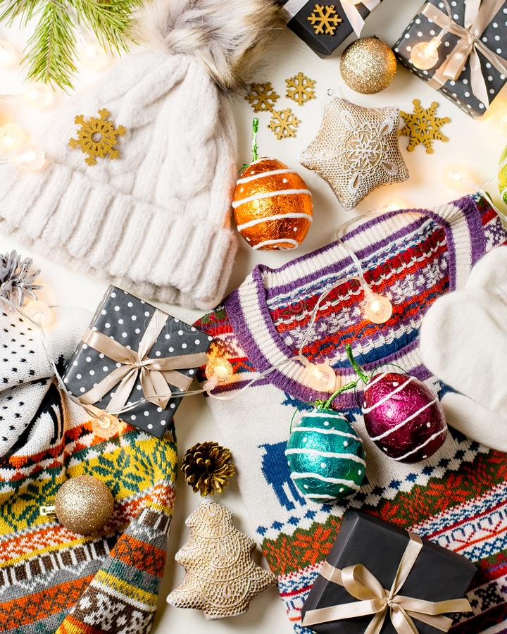 Christmas mood composition with Christmas sweater, hat, presents and lights. Winter concept flat lay, top view stock image