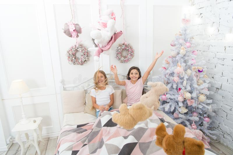 Christmas mood. Happy kids in bed at Christmas tree. Childhood games on xmas and new year. Little children enjoy stock photo