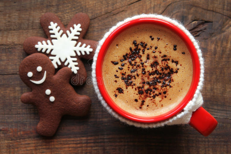 Christmas morning coffee and cookies. Good morning or Have a nice day Merry Christmas message concept - bright red cup of frothy coffee covered with a white royalty free stock photo