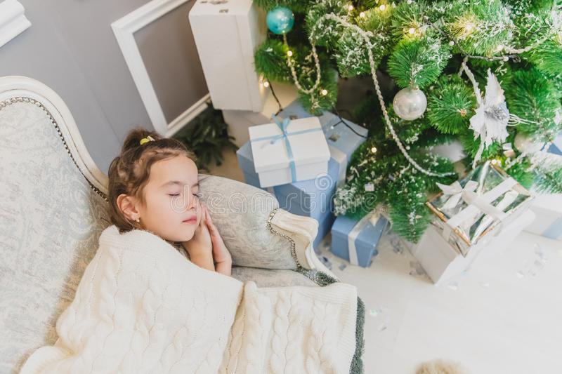 Angelic child daughter is sleeping on the sofa near Christmas tree with gifts. stock images