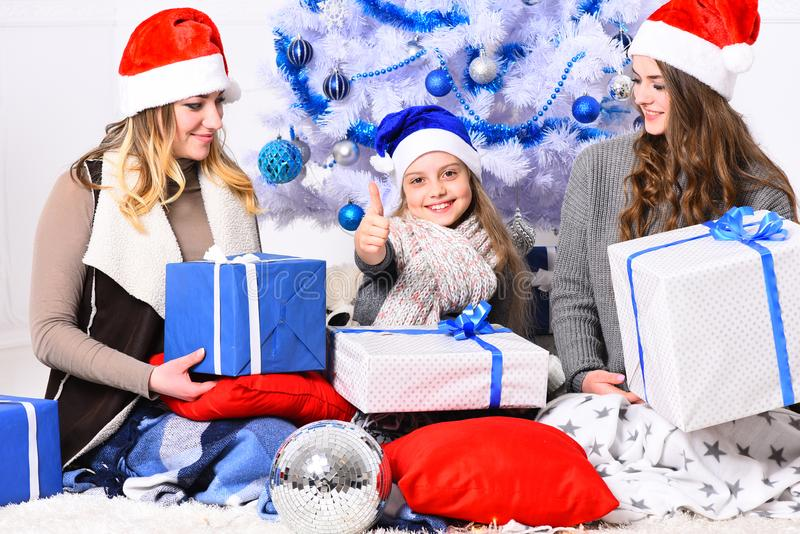 Christmas morning and New Year concept. Family or friends. In hats hold present boxes. Girls with happy faces show thumbs up near white and blue Christmas tree stock images