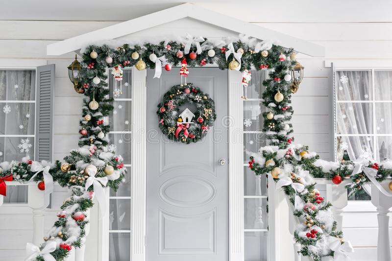 Christmas morning. porch a small house with a decorated door with a Christmas wreath. Winter fairy tale. Christmas morning. porch a small house with a decorated stock photo
