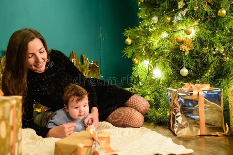 Christmas and mother concept. Christmas and people concept - mother and baby with gifts. On a Christmas background. warm christmas stock photo