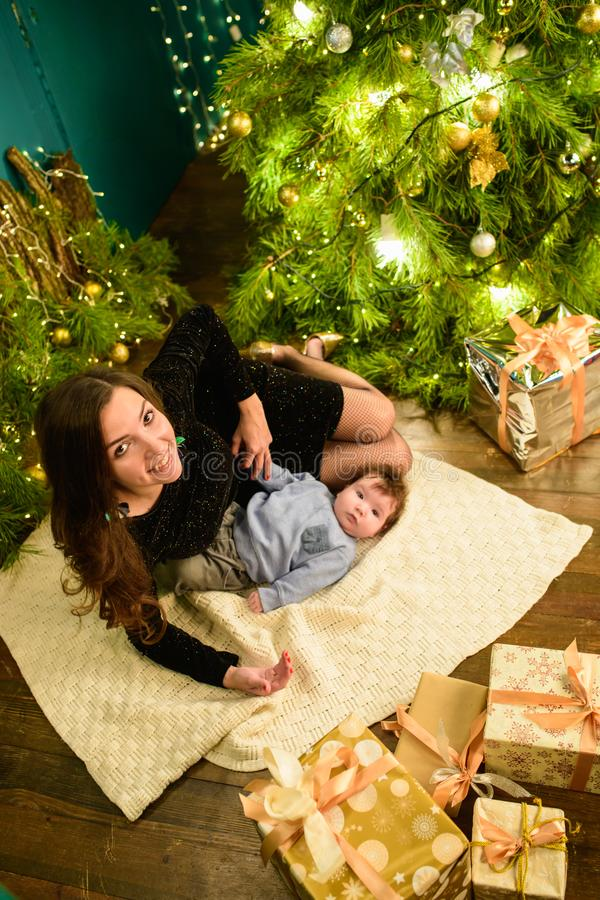 Christmas and mother concept. Christmas and people concept - mother and baby with gifts. On a Christmas background. warm christmas royalty free stock images