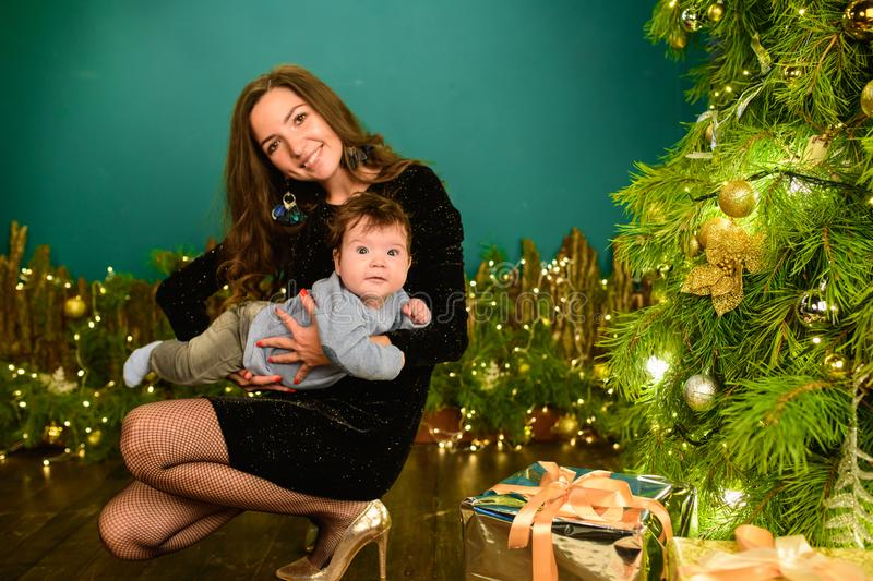 Christmas and mother concept. Christmas and people concept - mother and baby with gifts. On a Christmas background. warm christmas stock photos