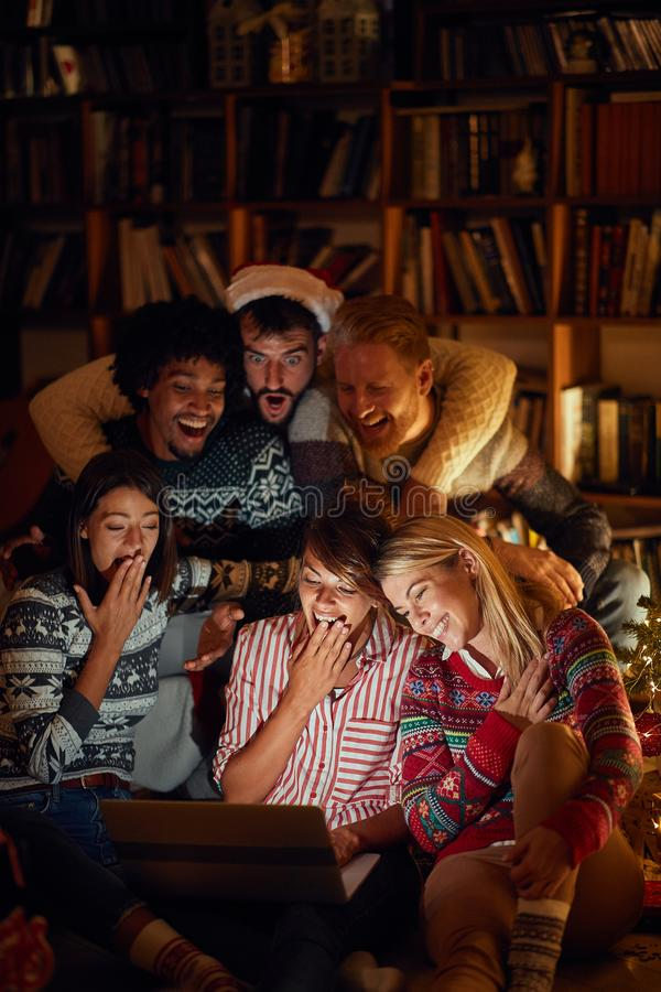 Christmas movie-young people watching laptop on Christmas eve stock photography