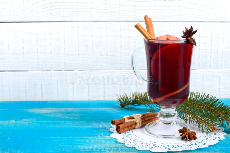 Christmas mulled red wine with spices and fruits on a blue wooden rustic table. Traditional hot drink with cinnamon, cardamom, stock images