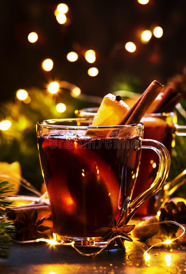 Christmas mulled red wine with spices and fruits on wooden rustic table. Traditional Christmas hot drink in festive light table royalty free stock photography