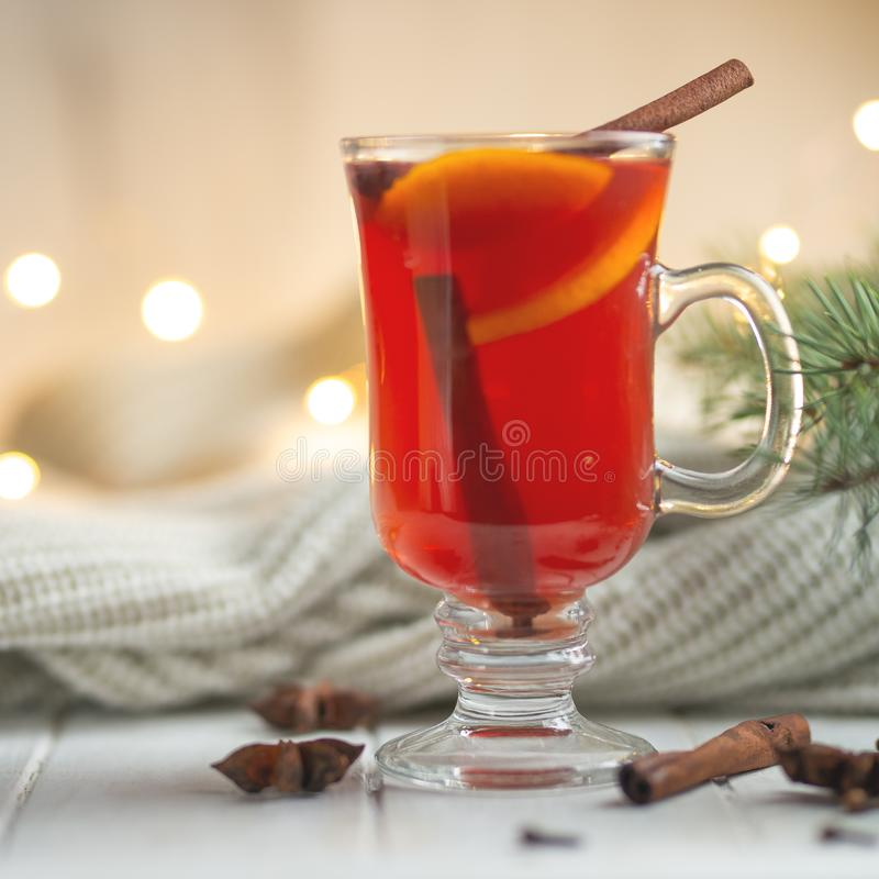 Christmas mulled red wine with spices and fruits on a wooden rustic table. Traditional hot drink in the New Year, with festive lig stock photography