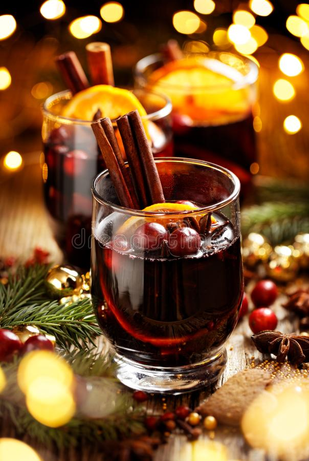 Christmas mulled red wine with spices and fruits on a wooden rustic table. Traditional hot drink at Christmas time royalty free stock image