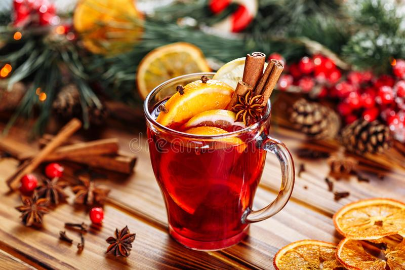 Christmas mulled red wine with spices and fruits on a wooden rustic table. Traditional hot drink at winter time royalty free stock photo