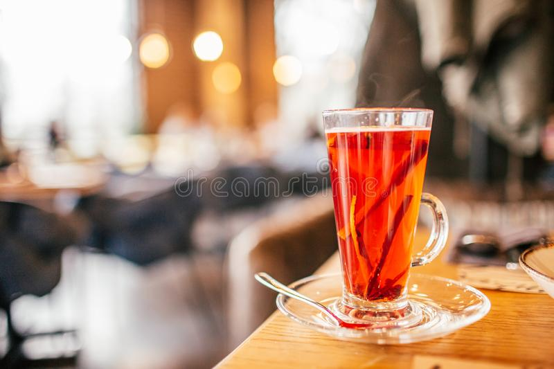 Christmas mulled red wine with spices and oranges on a wooden rustic table at restraunt. Traditional hot drink at Christmas punch royalty free stock photo