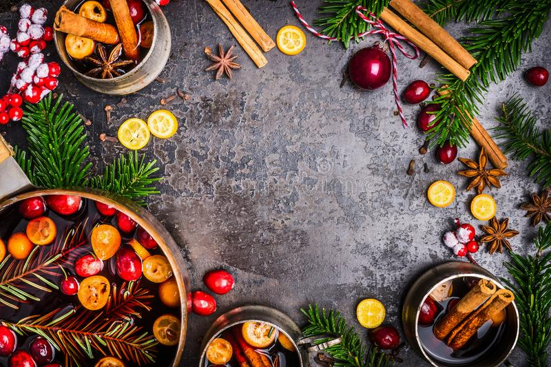 Christmas Mulled wine cooking preparation with pot, cups , ingredients and festive decorations on dark rustic background, top view. Frame. Christmas food stock photo