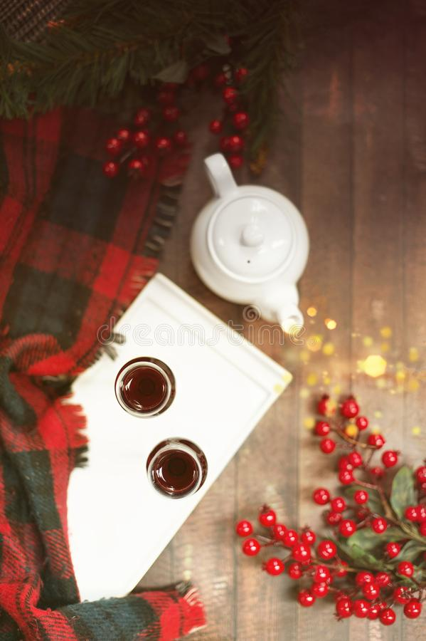 Christmas mulled wine cozy top view with blanket, two glasses and tea pot. With bokeh steam stock image