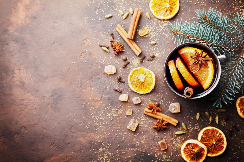 Christmas mulled wine or gluhwein with spices and orange slices on rustic table top view. Traditional drink on winter holiday. stock images