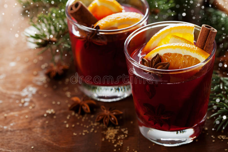 Christmas mulled wine or gluhwein with spices and orange slices on rustic table, traditional drink on winter holiday, magic light. Selective focus stock photos