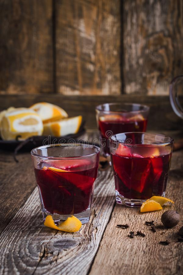 Christmas mulled wine with spices and oranges on wooden table, hot drinks stock photo