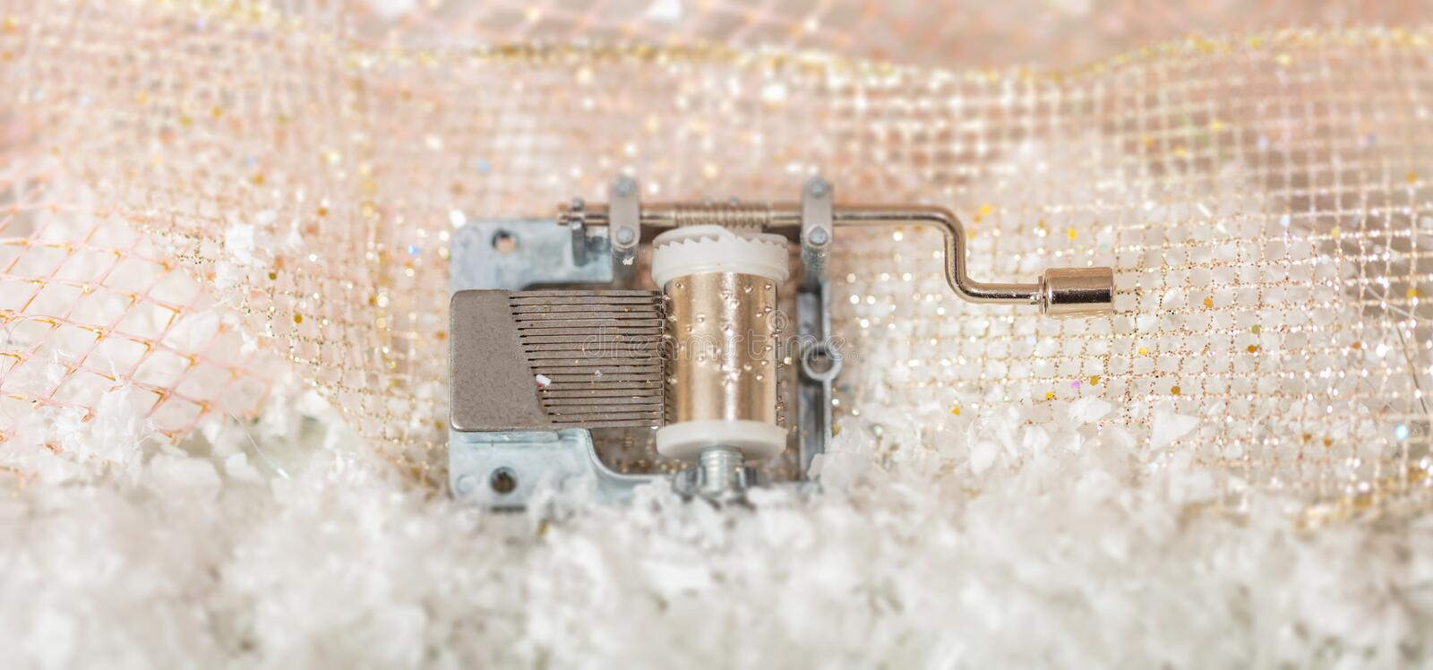 Christmas music box mechanism on snow, against abstract bokeh lights and glitter background. Banner royalty free stock image