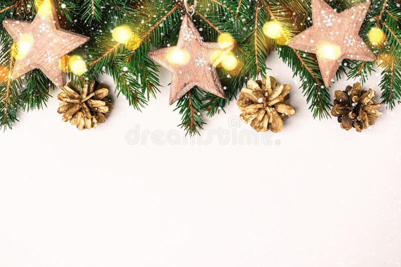 Christmas Nature Border of Fir Branches, wooden star toys and bokeh lights stock images
