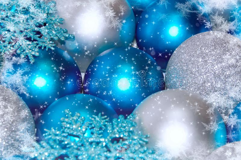 Christmas and New Year background. blue and silver sparkling balls, snowflake ornaments. With snow stock photo
