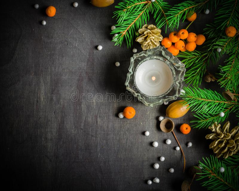 Christmas and New Year background. Christmas tree branch on a black background. Cones and fur-tree toys. View from above. stock photography
