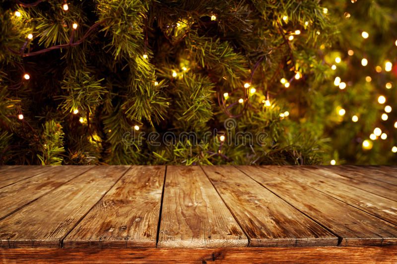 Christmas and New year background with empty dark wooden deck table over christmas tree and blurred light bokeh. royalty free stock images