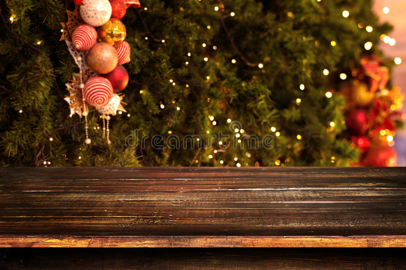 Christmas and New year background with empty dark wooden deck table over christmas tree and blurred light bokeh royalty free stock photos