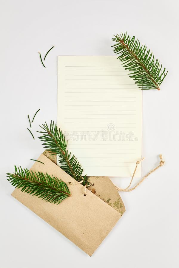 Christmas and New Year background. Fir branches and blank letter mockup in cardboard craft envelope over white background. Flat lay, top view royalty free stock photography